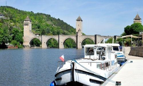 Le Pont Valentré et ces 3 tours dominent le Lot. Au premier plan est amarré deux bateaux de plaisance.