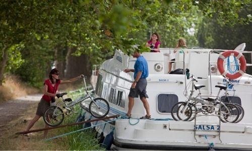 Une famille charge des vélos sur le ponton d'un bateau Le boat