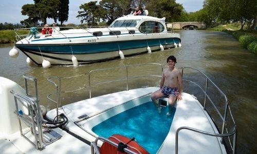 La piscinette d'un bateau de location de chez Nicols, un adolescent s'y baigne