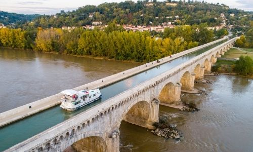 Le pont-canal de la Garonne en Aquitaine traversé par un bateau de location