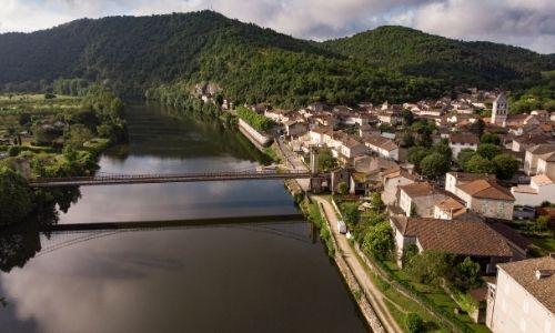 Une vue semi-aérienne du village de Douelle, du Lot et du pont suspendu qui le traverse