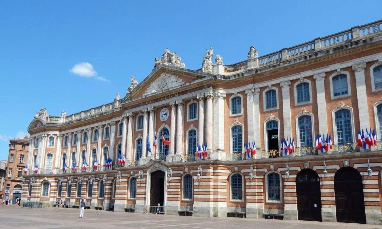 Façade du Capitole arborant des drapeaux français, la photo est prise en bié