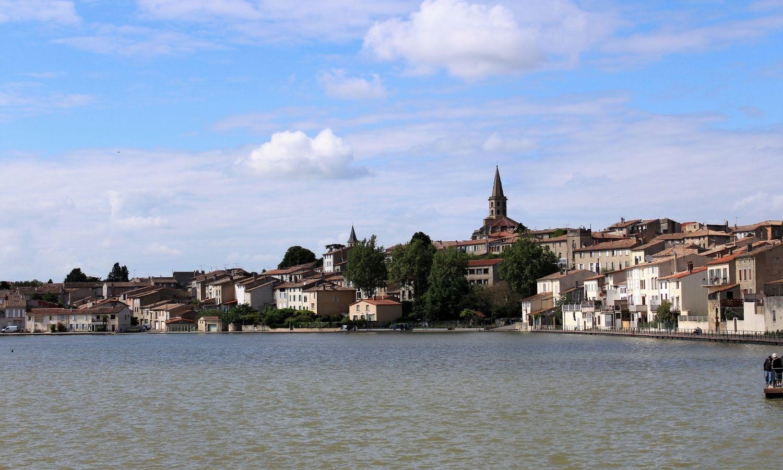 L'étendue d'eau du grand bassin de Castelnaudary s'étend jusqu'aux maisons de la ville. Son église culmine au-dessus des habitations.