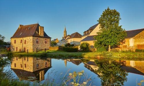 Les berges du village de Tinténiac, on peut apercevoir le clocher de l'église derrière les maisons en pierre.