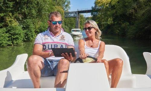 Un couple sur le poste de navigation extérieur de leur bateau sans permis