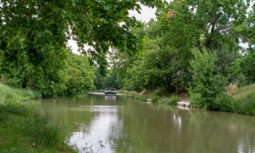 Une péniche navigue sur le Canal du Midi, la nature alentour berce la photo dans un climat de tranquillité