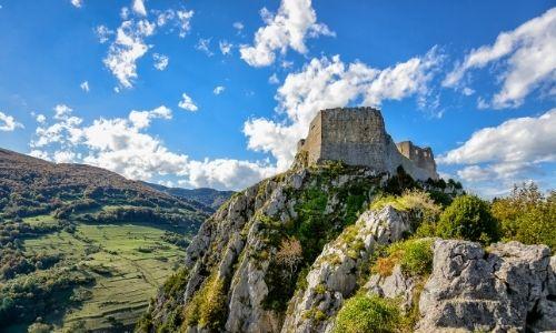 Un château Cathare moyennement conservé est perché sur une colline rocheuse.