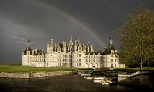 La château de Chambord perdu dans son vaste parc. Un arc en ciel culmine au-dessus du château.