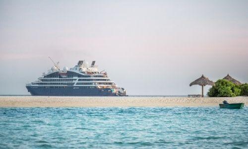 Le Jacques Cartier au loin et un plage paradisiaque au premier plan