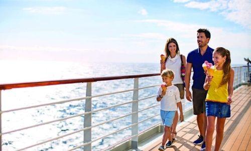 Deux adultes et deux enfants qui se baladent sur le pont supérieur d'un bateau, en dégustant une glace