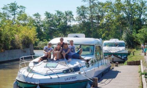 Un groupe d'amis sur le ponton principale d'un bateau sans permis se réuni pour une belle photo