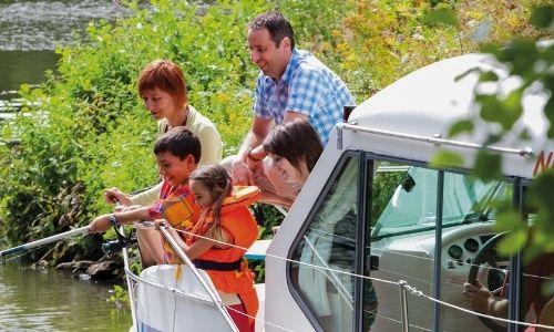Une famille s'amuse sur le pont de leur bateau sans permis, l'instant est intime et convivial