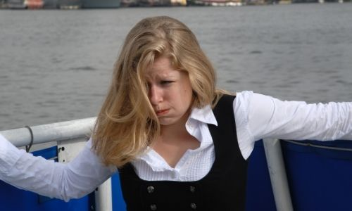 Une dame sur un petit bateau ayant le mal de mer