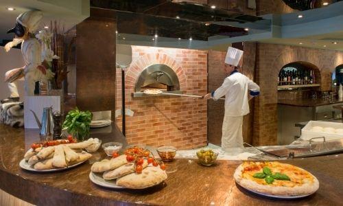 Pizzéria à bord d'un navire de croisière, un cuisinier enfourne des pizzas au four